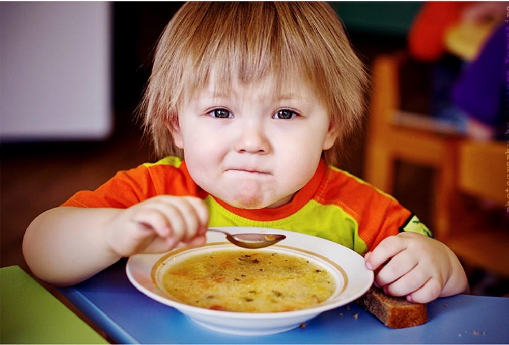 Ребенок ест ложкой суп