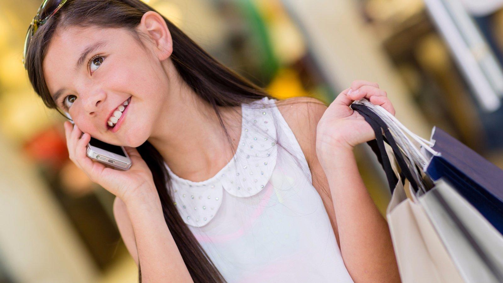 Довольная девочка говорит по телефону