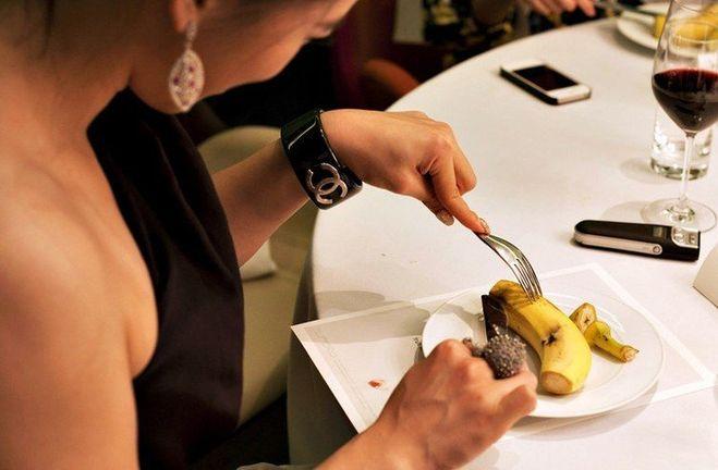 Девушка очищает банан вилкой
